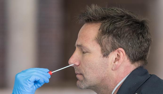 A man receives a swab test for COVID-19
